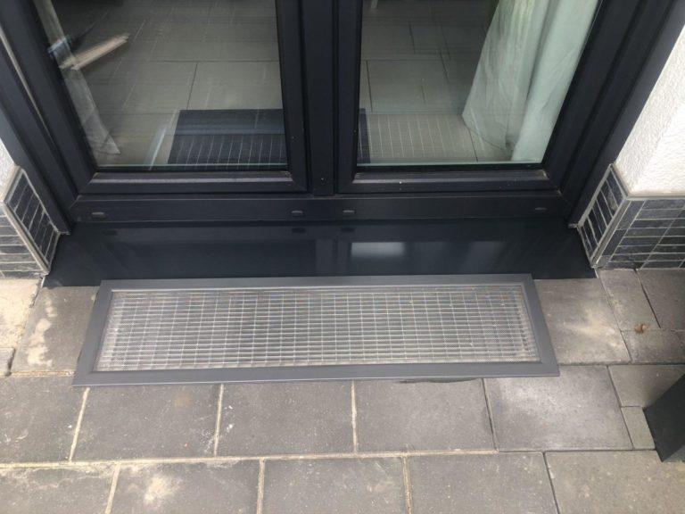 Lichtschachtabdeckung vor einer Balkontür